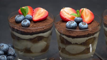 ягода : Classic tiramisu dessert with blueberries and strawberries on stone serving board on concrete Стоковые видеозаписи