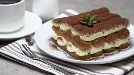 çatallar : Classic tiramisu dessert on ceramic plate, milk or cream and cup of coffee on concrete background Stok Video