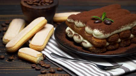 çatallar : Classic tiramisu dessert and savoiardi cookies on ceramic plate on wooden background Stok Video