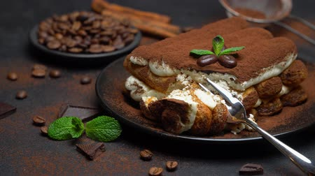 çatallar : portion of Classic tiramisu dessert on ceramic plate on concrete background Stok Video