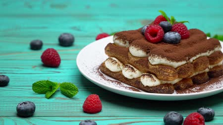 jagody : portion of Classic tiramisu dessert with raspberries and blueberries on wooden background Wideo