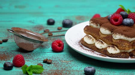 fincan tabağı : portion of Classic tiramisu dessert with raspberries and blueberries on wooden background Stok Video