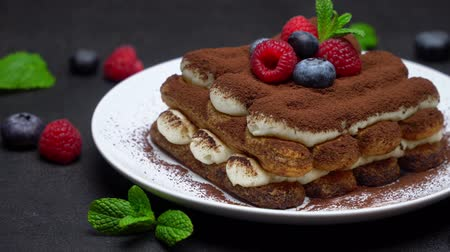 fincan tabağı : portion of Classic tiramisu dessert with raspberries and blueberries on dark concrete background Stok Video