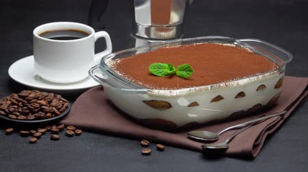 spoons : Tiramisu dessert in glass baking dish, cup of espresso and coffee maker on concrete background Stock Footage