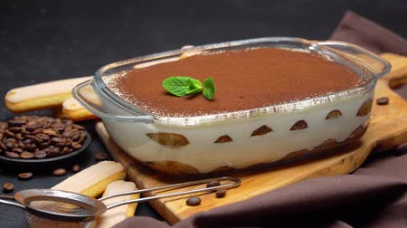 разделочная доска : Tiramisu dessert in glass baking dish on wooden board and savoiardi cookies on concrete background