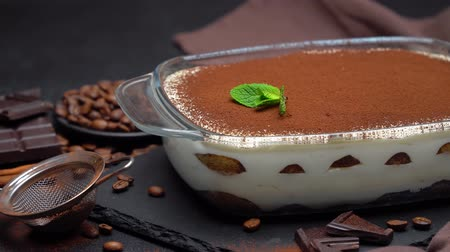 serving board : Tiramisu dessert in glass baking dish and pieces of chocolate bar on concrete background Stock Footage