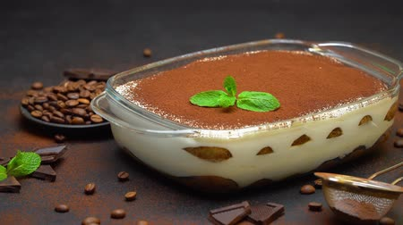 vla : Tiramisu dessert in glass baking dish and pieces of chocolate bar on concrete background Stockvideo