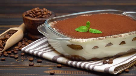 italian coffee : Traditional Italian Tiramisu dessert in glass baking dish and coffee beans on wooden background