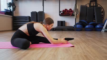 trecho : 4x slow motion video of Beautiful young woman working out and stretching indoors