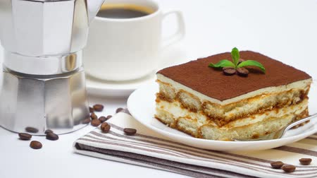 tampas : Tiramisu dessert portion, mocha coffee maker and cup of fresh espresso coffee on white background