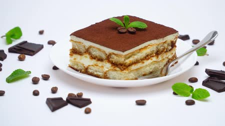 crema pasticcera : Tiramisu dessert portion, pieces of chocolate bar and coffee beans isolated on white Filmati Stock