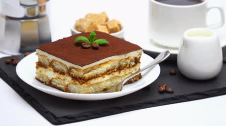 menta : Tiramisu dessert portion, mocha coffee maker, milk or cream, sugar and cup of fresh espresso coffee