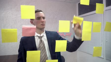 решение : Young businessman sticking sticky notes in office Стоковые видеозаписи