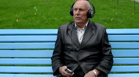 dikmek : Old man listening to music sitting on the bench in the park