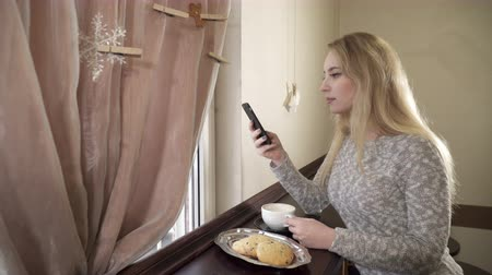 latte macchiato : young woman sitting in cafe and using her phone