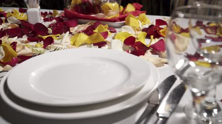 plated : Closeup of table with plates decorated with rose petals in the restaurant