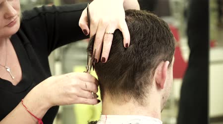 estilista : Hair stylist is making a haircut for a young man
