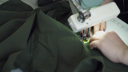 parecer : Closeup of woman sewing green fabric with the sewing machine