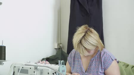 parecer : Blonde woman sewing working on the clothing factory