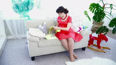 crawlers : Pregnant woman choosing clothes for her baby on the couch