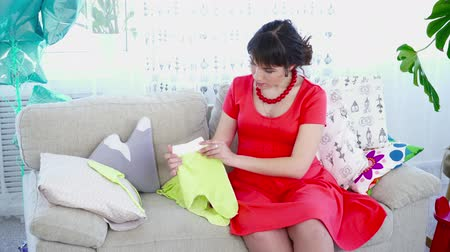 crawlers : Pregnant woman choosing clothes for her baby on the couch in the livingroom