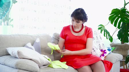 crawlers : Young pregnant woman choosing clothes for her baby on the couch Stock Footage