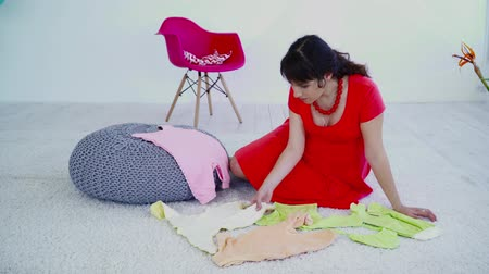crawlers : Pregnant woman sitting on the carpet and choosing clothes for future baby