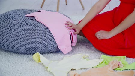 crawlers : Pregnant woman sitting on the carpet and choosing clothes for future baby closeup