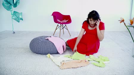 crawlers : Pregnant woman sitting on the carpet, talking on the phone and choosing clothes for future baby Stock Footage