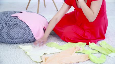 crawlers : Young pregnant woman sitting on the carpet, talking on the phone and choosing clothes for future baby