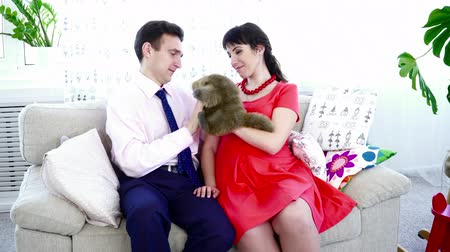 apaság : Pregnant woman in a red dress playing with her husband with a toy