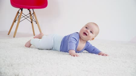 bakıyorum : Pretty little baby boy of 6 months laying on the carpet