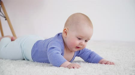 bakıyorum : Pretty little baby boy of 6 months laying on the carpet closeup