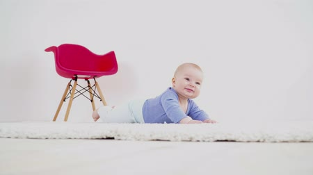 bakıyorum : Pretty cute baby boy of 6 months laying on the carpet Stok Video