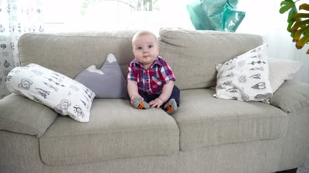 bakıyorum : Small cute baby boy sitting on the sofa and looking around