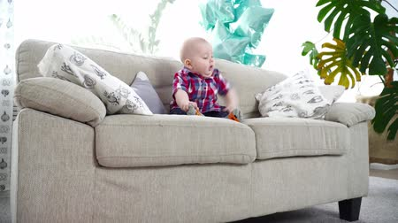 bakıyorum : Small cute baby boy in the shirt sitting on the sofa