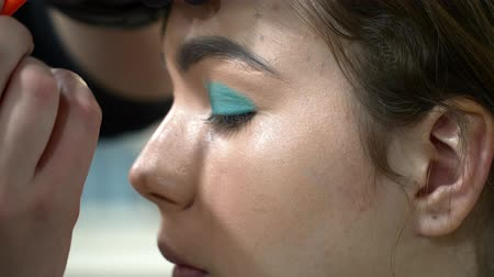 supermodel : Man makeup artist making the face art with blue shadows Stock Footage