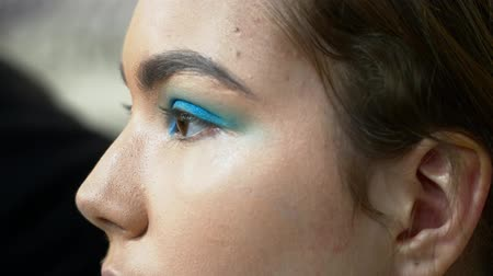 supermodel : Man makeup artist making the face art with blue shadows for a woman closeup Stock Footage