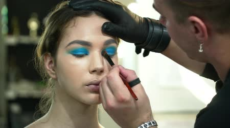 supermodel : Man makeup artist making the face art with blue shadows in gloves