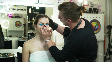 supermodel : Man makeup artist making the face art with blue shadows in front of the mirror in salon
