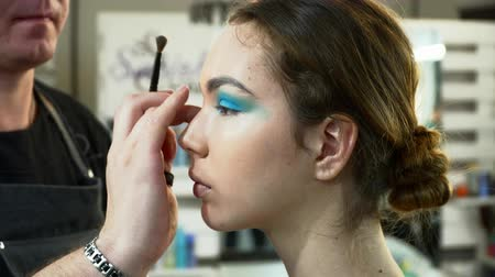 supermodel : Man makeup artist making the face art with blue shadows in beauty studio