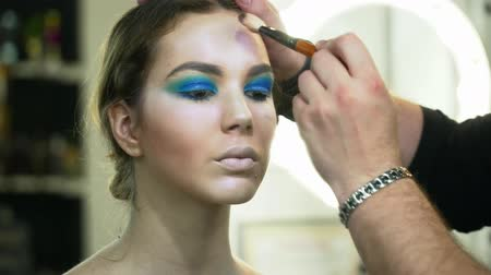 supermodel : Makeup artist making beautiful face art for a young brunette woman with makeup brush Stock Footage