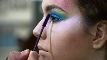 supermodel : Makeup artist making beautiful face art for a young brunette woman, painting eyelashes