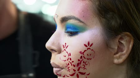 supermodel : Makeup artist making face art with a stencil with red flowers closeup