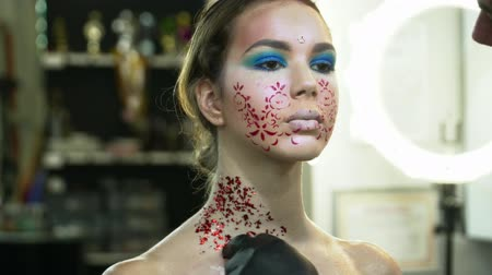 supermodel : Makeup artist covering womans body with the sparkles,body art