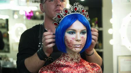 supermodel : Makeup artist putting on the wig and a crown to a woman
