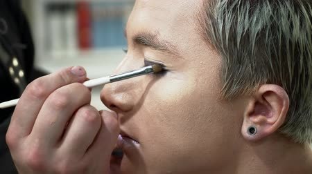 supermodel : Makeup artist making face art for a young blonde man, painting eyes Stock Footage