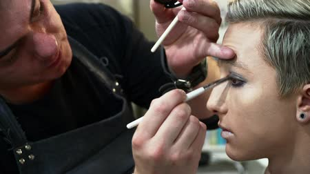 supermodel : Male makeup artist making face art for a young blonde man