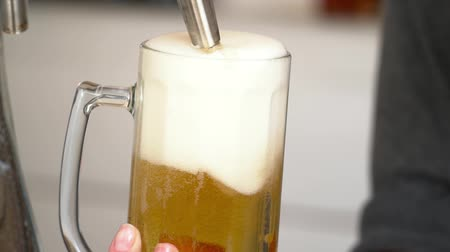 musluk : Closeup of barman pouring beer with foam into the glass slow motion