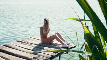 platform edge : Young woman relaxing near the lake during the summer Stock Footage